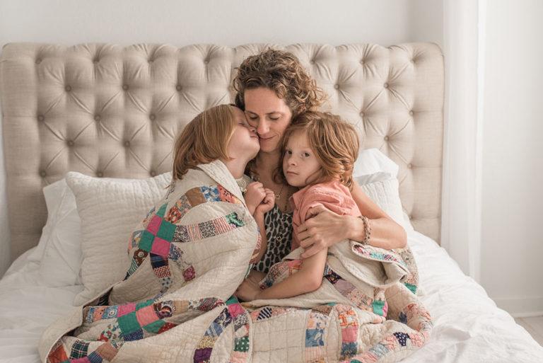 Nyskilt kvinde omfavner sine børn i en seng